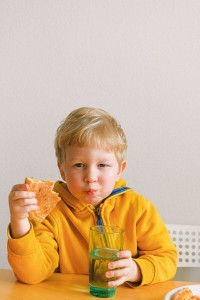 Boy Wearing Yellow Hoodie Eating Pizza And Holding A Glass 3905792